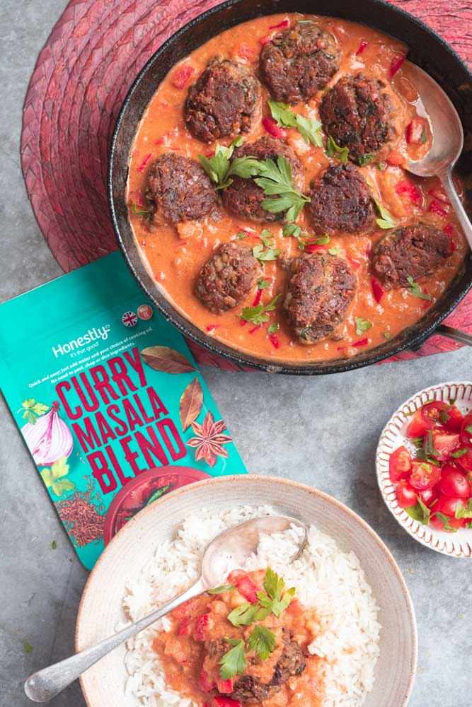 Lentil Koftas in a pan with curry sauce.  With a packed of Curry Masala blend by Honestly