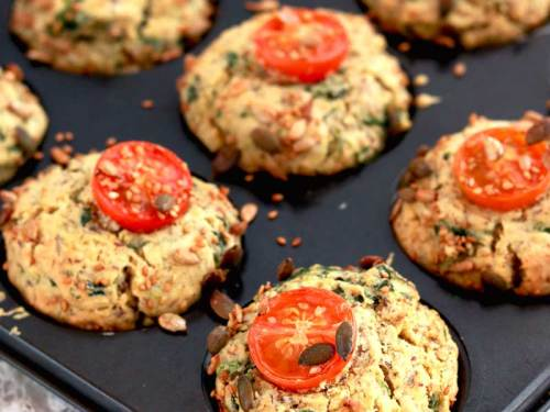 Vegan Spinach Muffin in a tin topped with cherry tomatoes