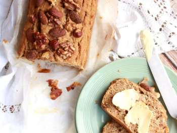 Vegan Banana Bread with a slice cut off and buttered