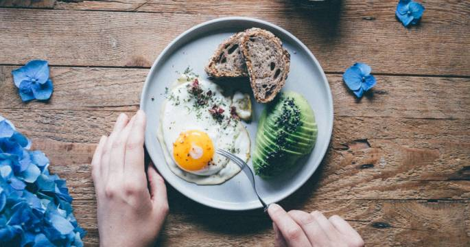 Person eating a veggan meal of 1 sunnyside up egg, avocado, and 2 slices of whole-grain toast.