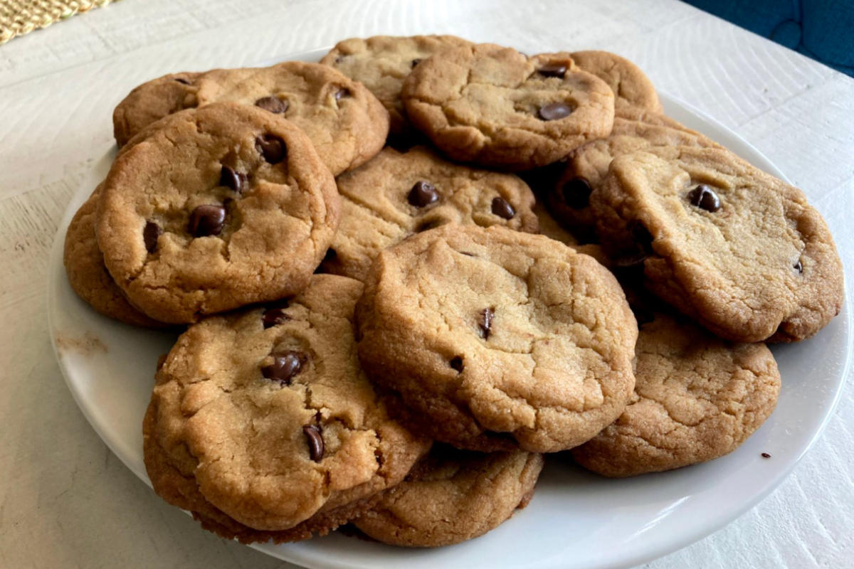 A plate full of vegan chocolate chip cookies, tollhouse style on a distressed white wooden table/
