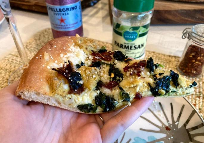 Vegan white pizza slice with tofu ricotta, spinach and sun-dried tomatoes topped with parmesan and paired with Pellegrino.