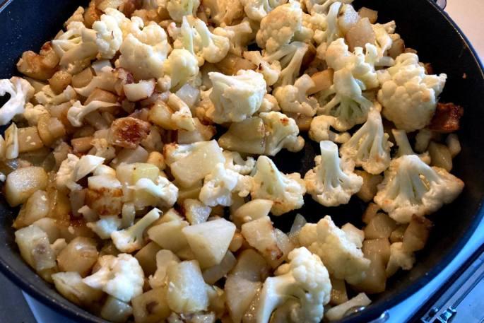 Potatoes and cauliflower cooking on a pan for vegan aloo gobi.