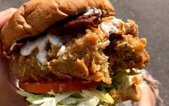 Bite taken of the Atlas Monroe vegan fried chicken sandwich.