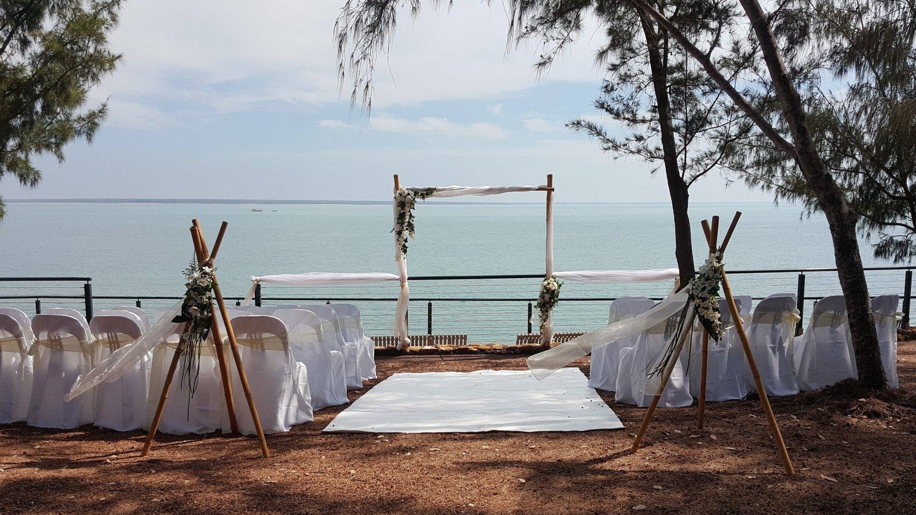 outdoor wedding ceremony; bamboo frame; bamboo tripods; white and ivory; white runway carpet; ocean view; darwin harbour; Dudley Point; fannie bay
