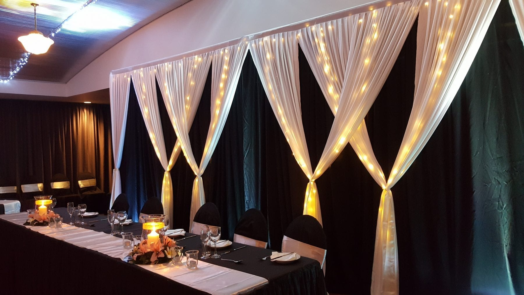 black & ivory backdrop; fairy lights; hurricane vase; pink flowers; fannie bay