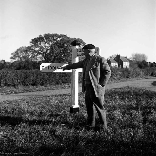 A black and white image of a man dressed in farmer's clothing, pointing at the sign that says 'Chiddingly'