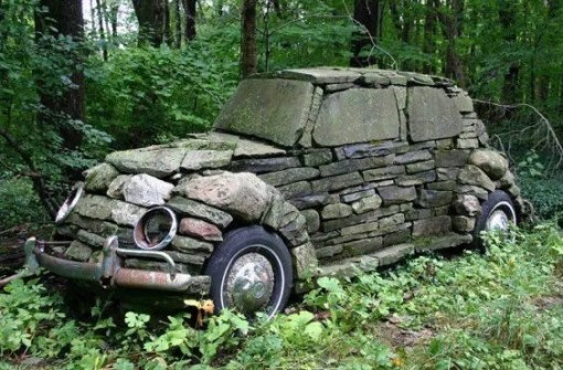 Black Volkswagen Beetle Covered in Stone