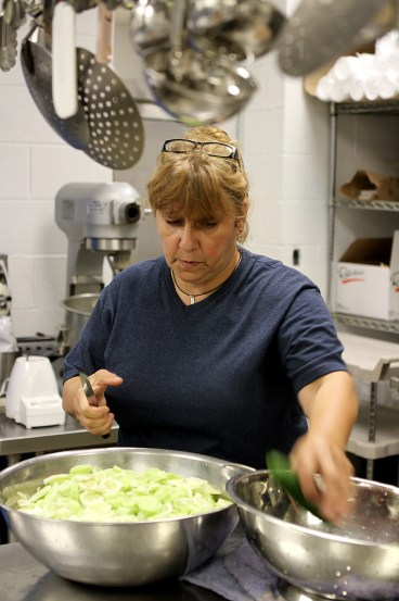 Food Service Director for Vienna High School Betty Saltzman prepares a cucumber salad Monday morning from the fresh supply of produced delivered to the school through the Dixon Springs Impact Incarceration Program.  Saltzman said the school has received several hundred pounds of fresh produce through the Dixon Spring's garden program allowing the school to save money and offer a healthier choice of foods at lunch.  Excess produce, such as tomatoes and green beans, has been frozen for future use.