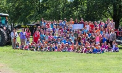 Superintendent Paige Maginel and Monsanto representative Kevin Reagan holding $25,000 Grow Rural Education check with Dongola USD 66 students, faculty and staff.