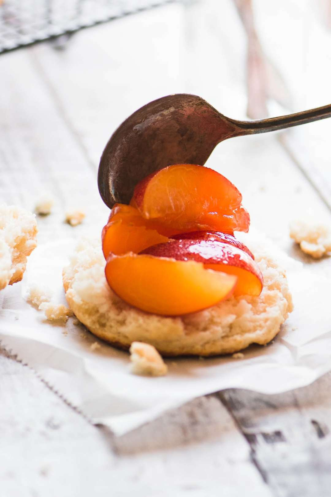 spooning peaches over biscuits for fresh peach shortcake