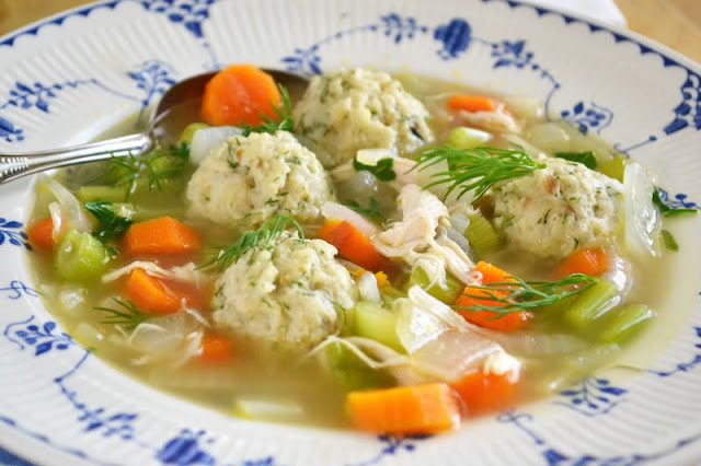 Photo of a bowl of dilled matzo ball soup.