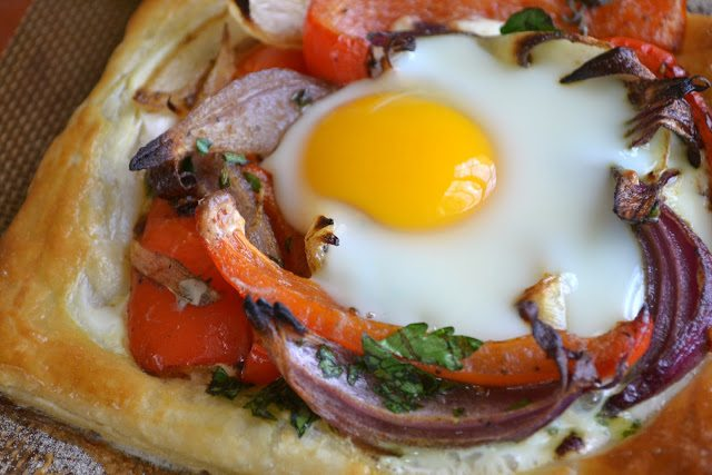 Close up photo of a red pepper and baked egg galette on a baking tray