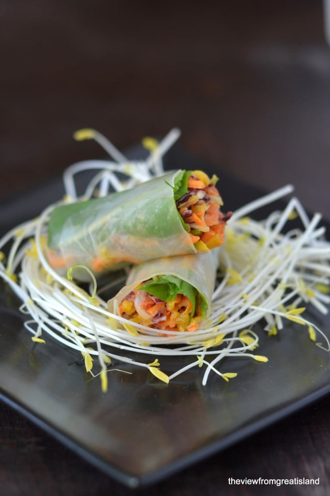 Spicy Asian Slaw Summer Rolls on a bed of pea shoots on a black plate.