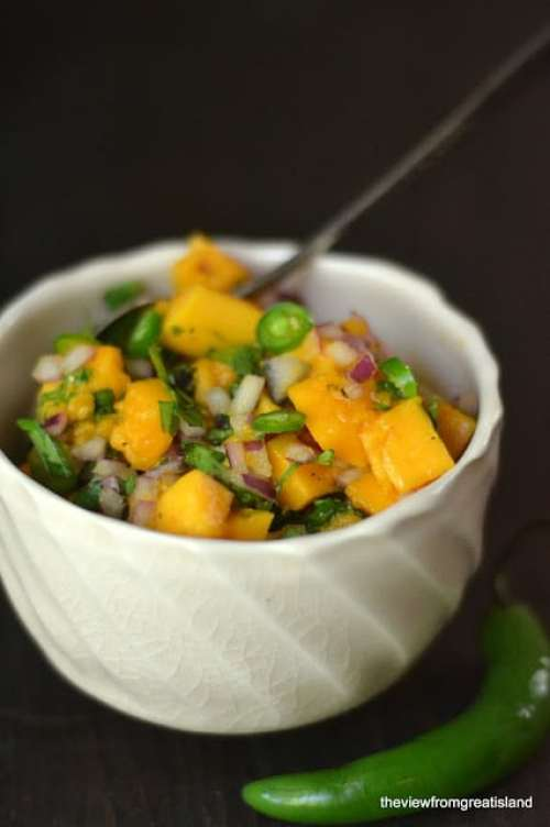 a small bowl of papaya salsa with spoon