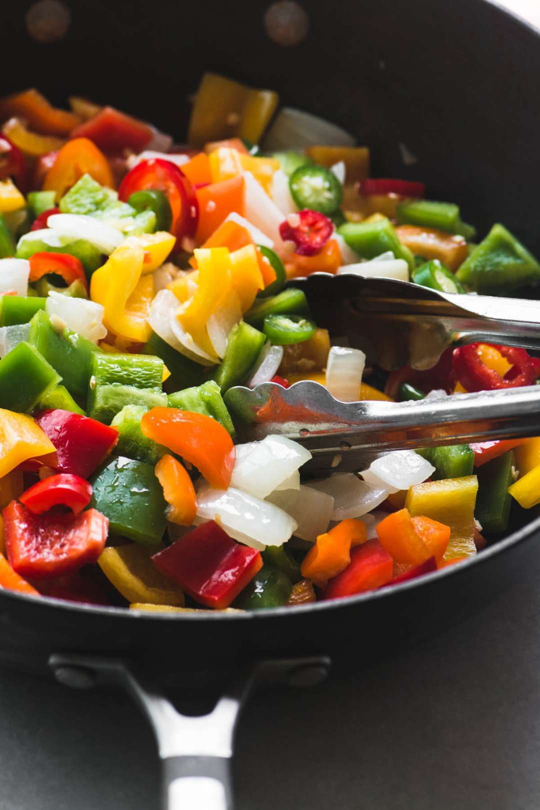 Stir frying colorful peppers in a wok for Firecracker Chicken