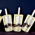 A line of chunky peanut butter cup pudding popsicles against a dark blue background.