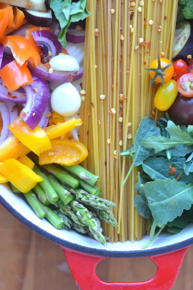 vegetables and spaghetti layered in a red pot for one pot farmers market pasta