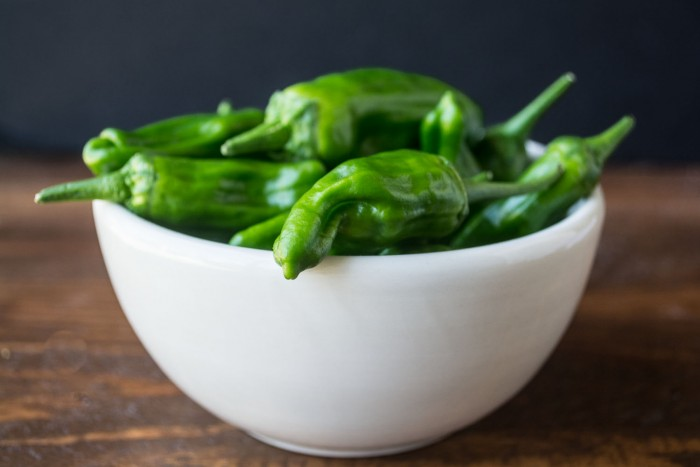 Photo of a white bowl filled with shishito peppers.