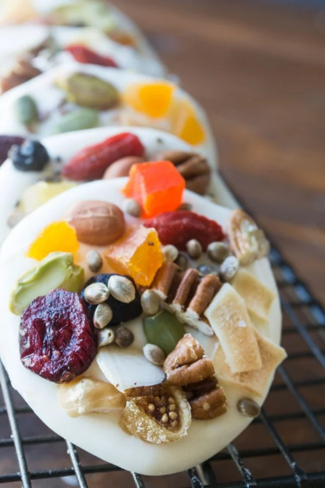 White chocolate rounds topped with healthy fruit, nuts, and seeds