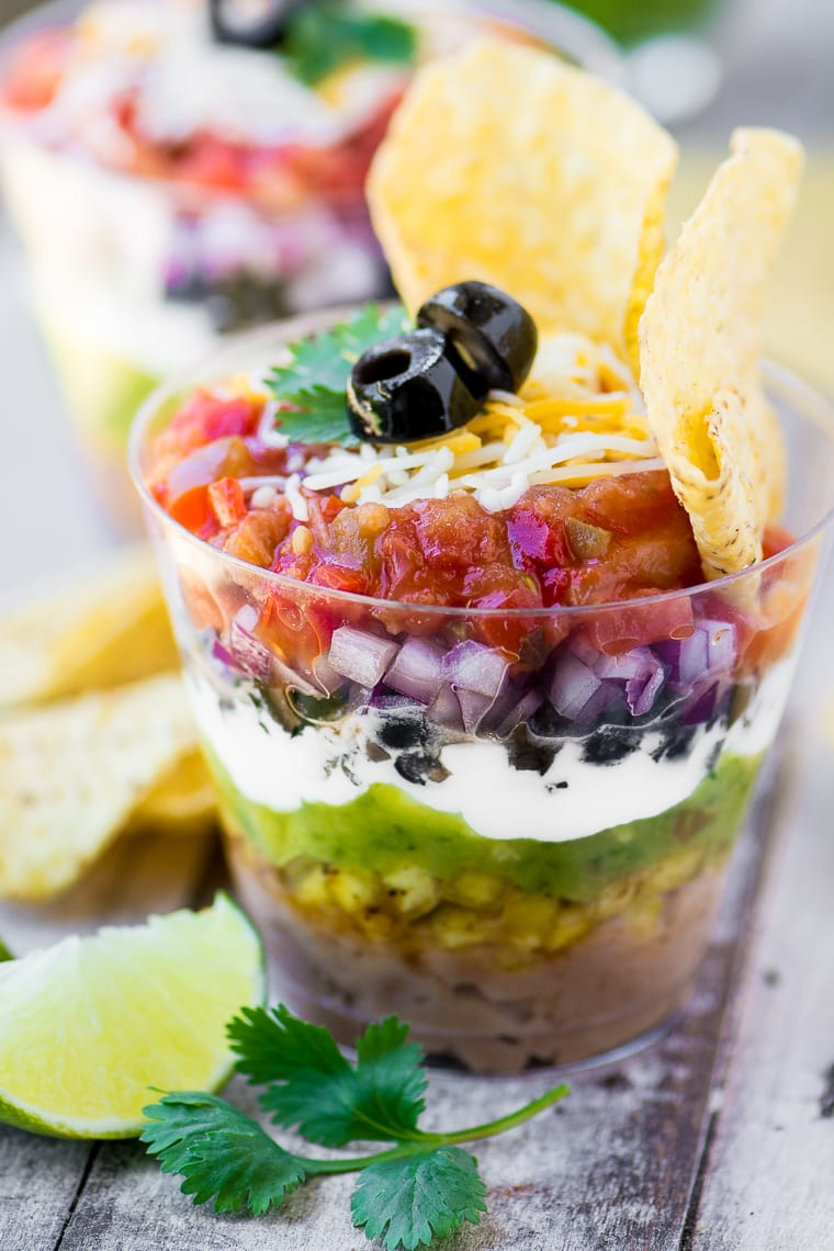These colorful 7 Layer Dip Cups are portable little appetizer stations layered up just like everybody's favorite Tex-Mex bean dip ~ these colorful appetizers will be the hit of your next party!