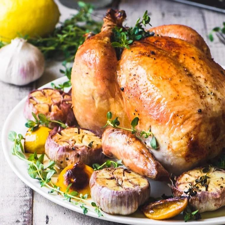 Roast chicken with purple garlic on a platter
