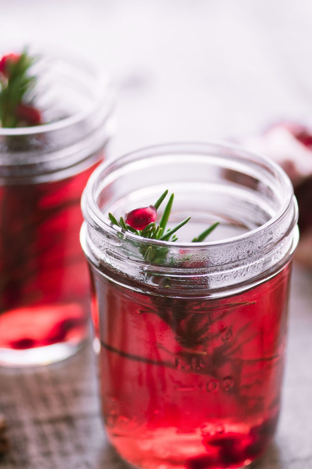 Mulled Pomegranate Cider in a mason jar with rosemary sprig