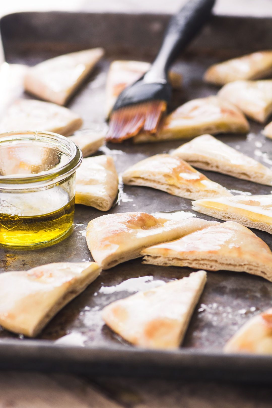 Brushing homemade pita chips with olive oil