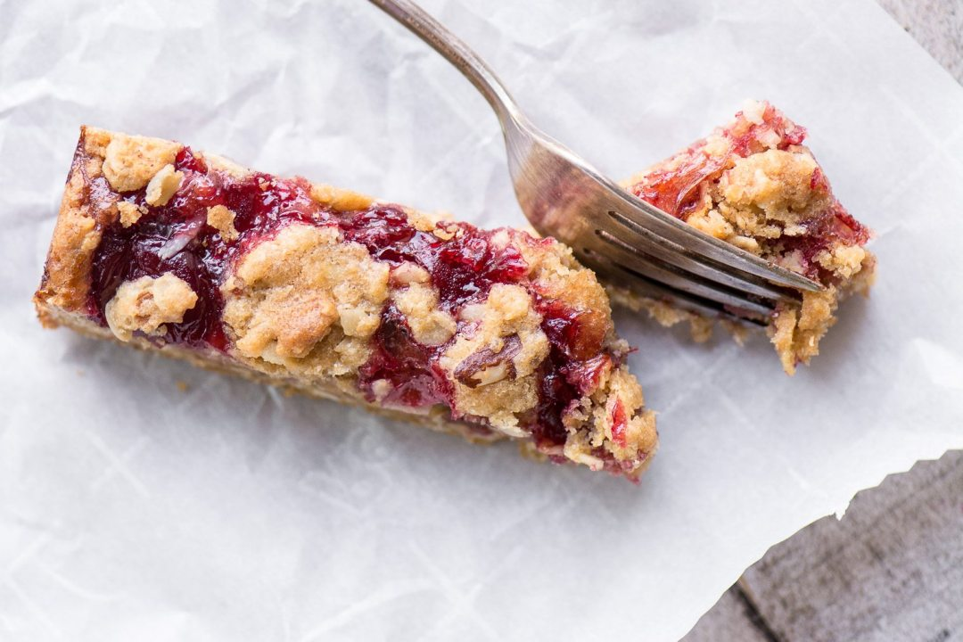 Sour Cherry Almond Bar with fork on parchment paper