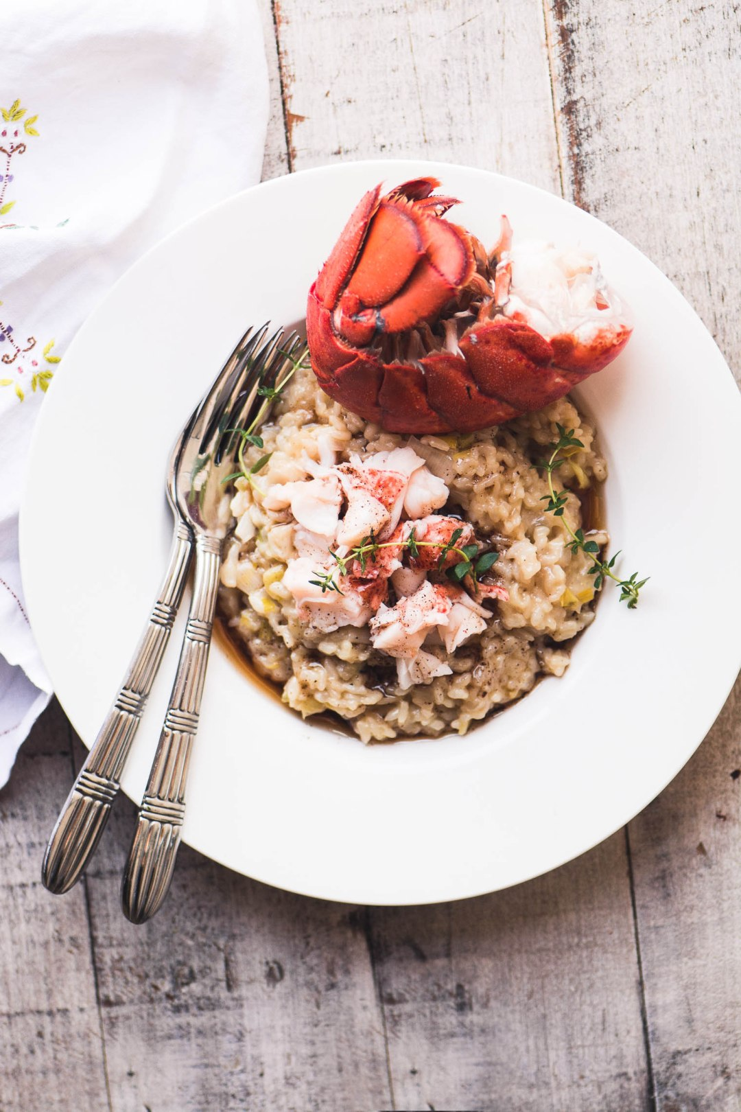 Instant Pot Lobster Risotto in a white bowl with lobster tail