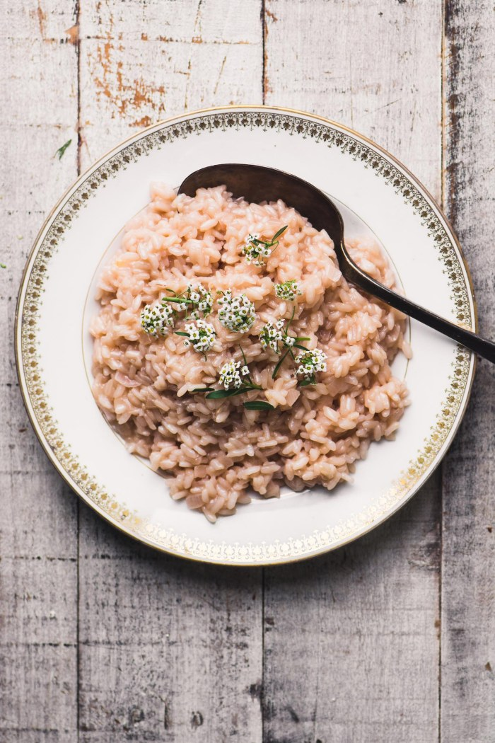 Rosé risotto in a white bowl on a wooden table