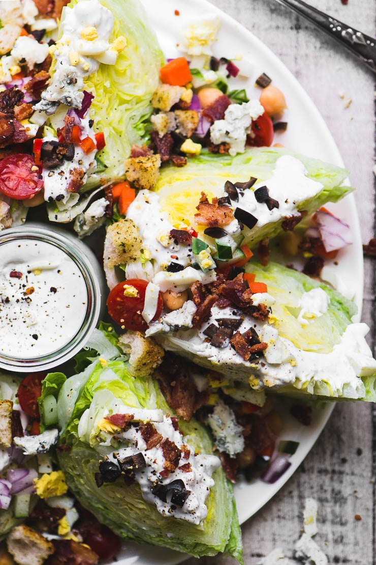 Hearts of iceberg lettuce in a fully loaded wedge salad platter