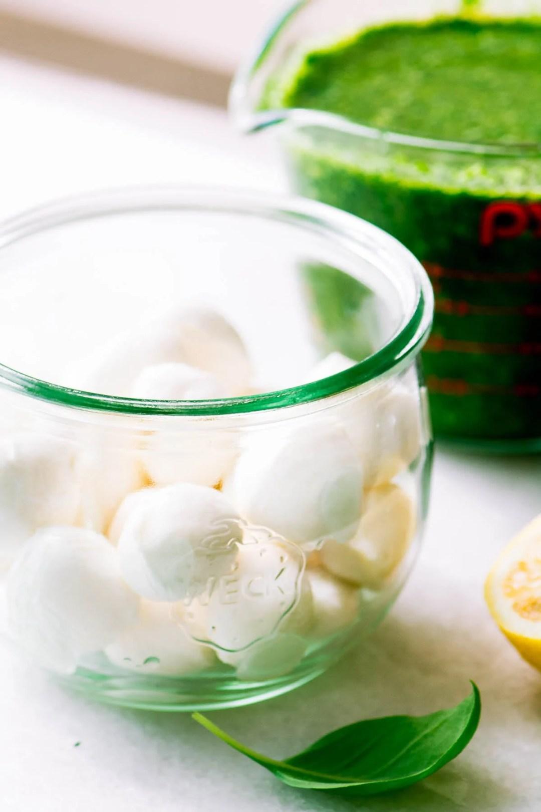 a jar of mozzarella balls and basil marinade