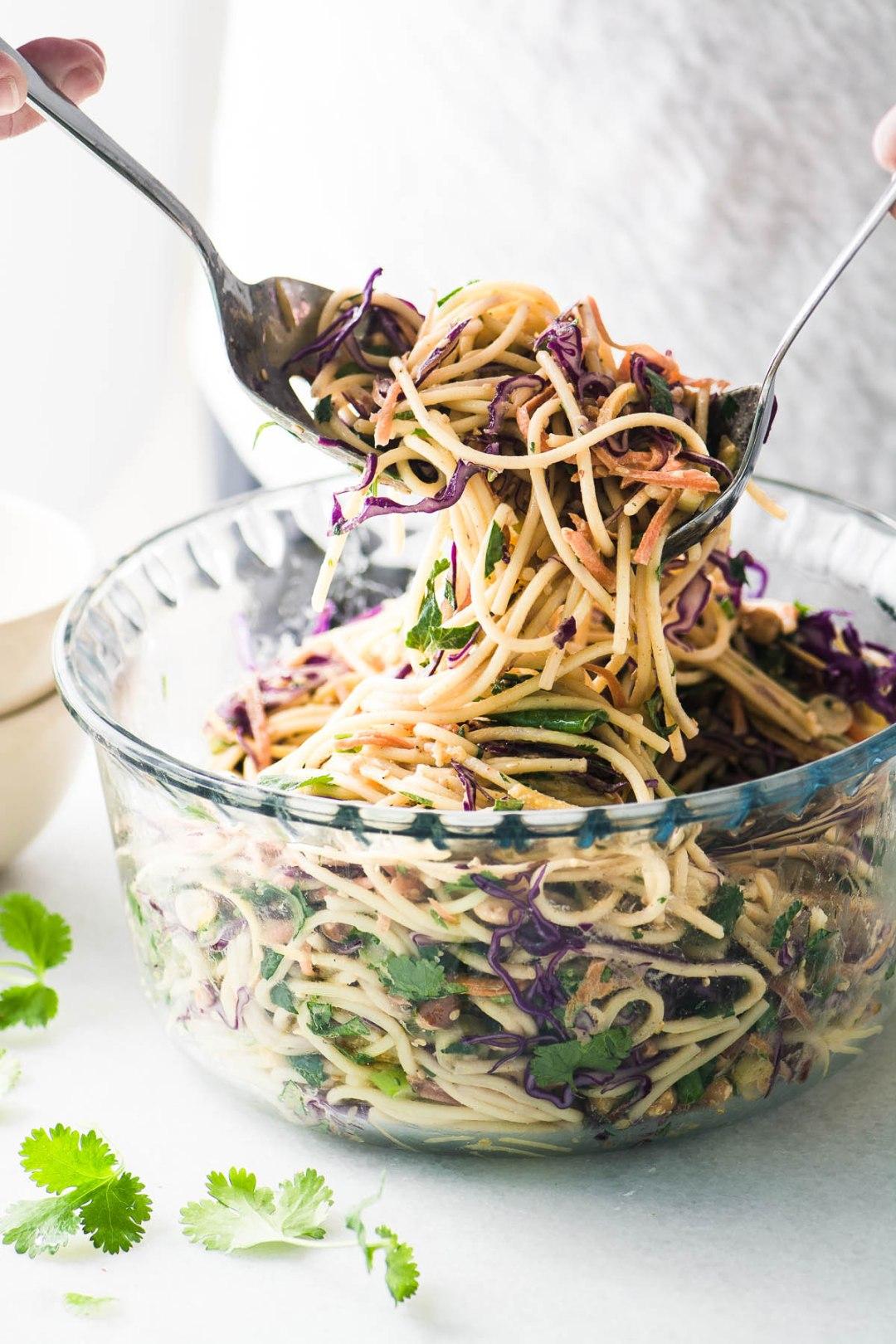 Toassing a spicy Thai spaghetti salad
