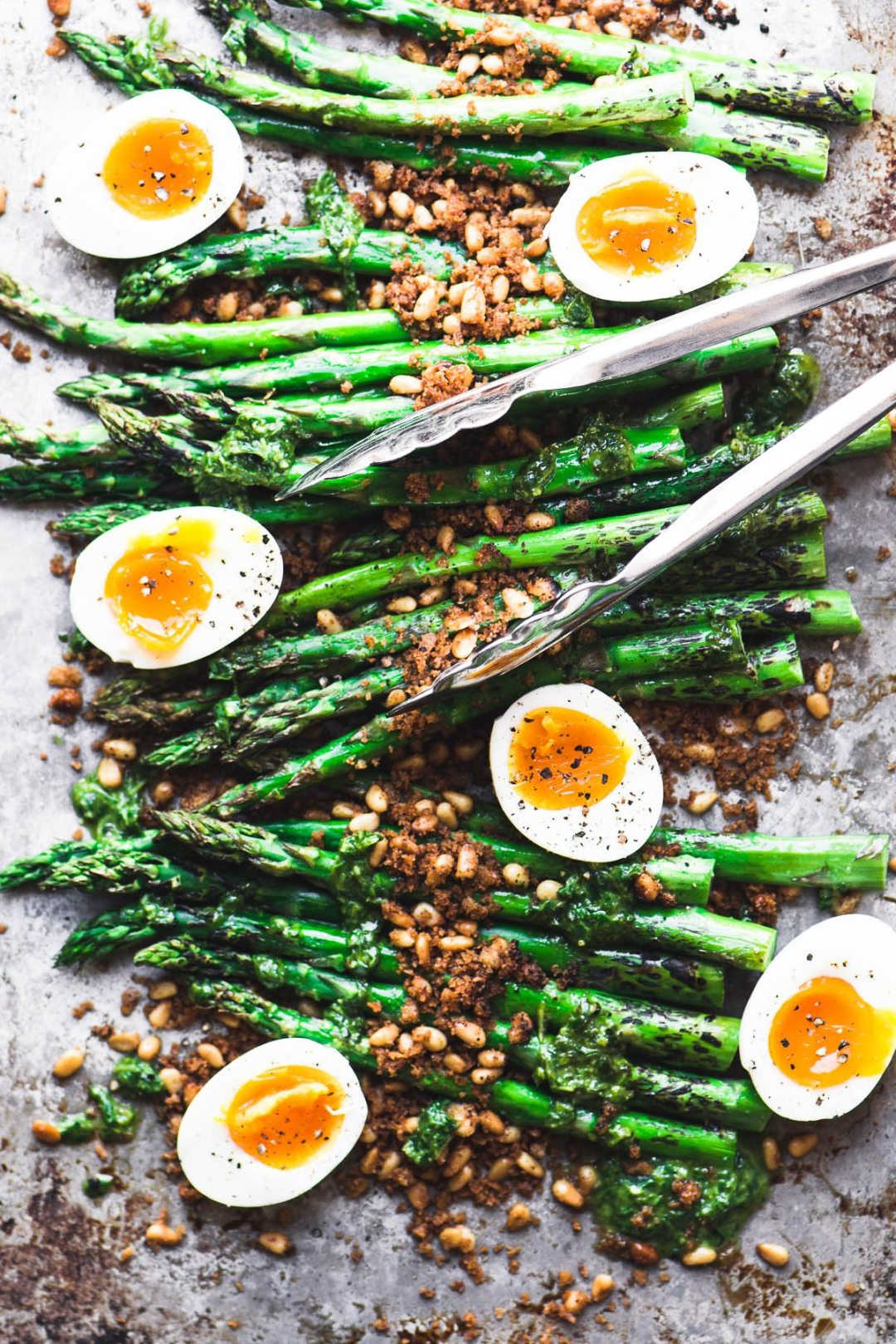 Easy Roasted Asparagus on a baking pan with runny eggs