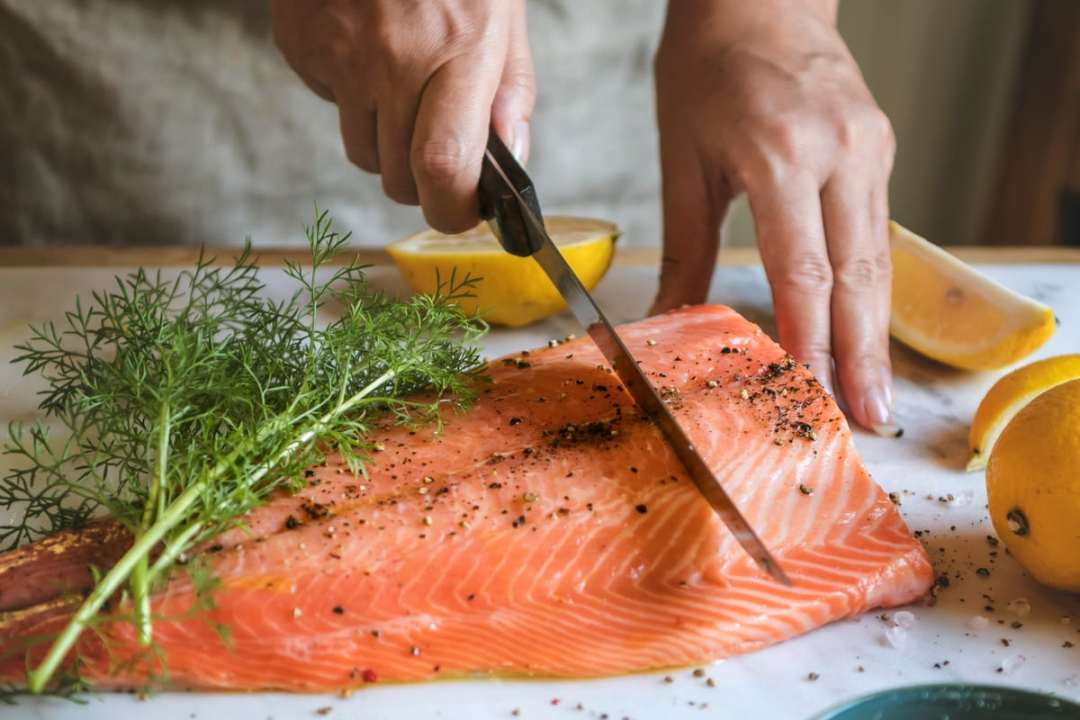 slicing a whole side of salmon