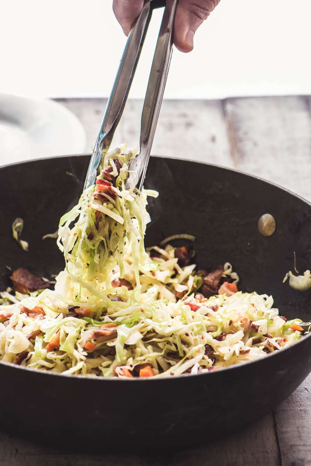 A skillet with fried cabbage and bacon slaw