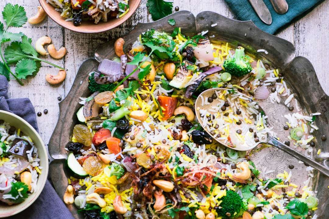 overhead photo of peach and cashew biryani salad on a silver platter with large spoon