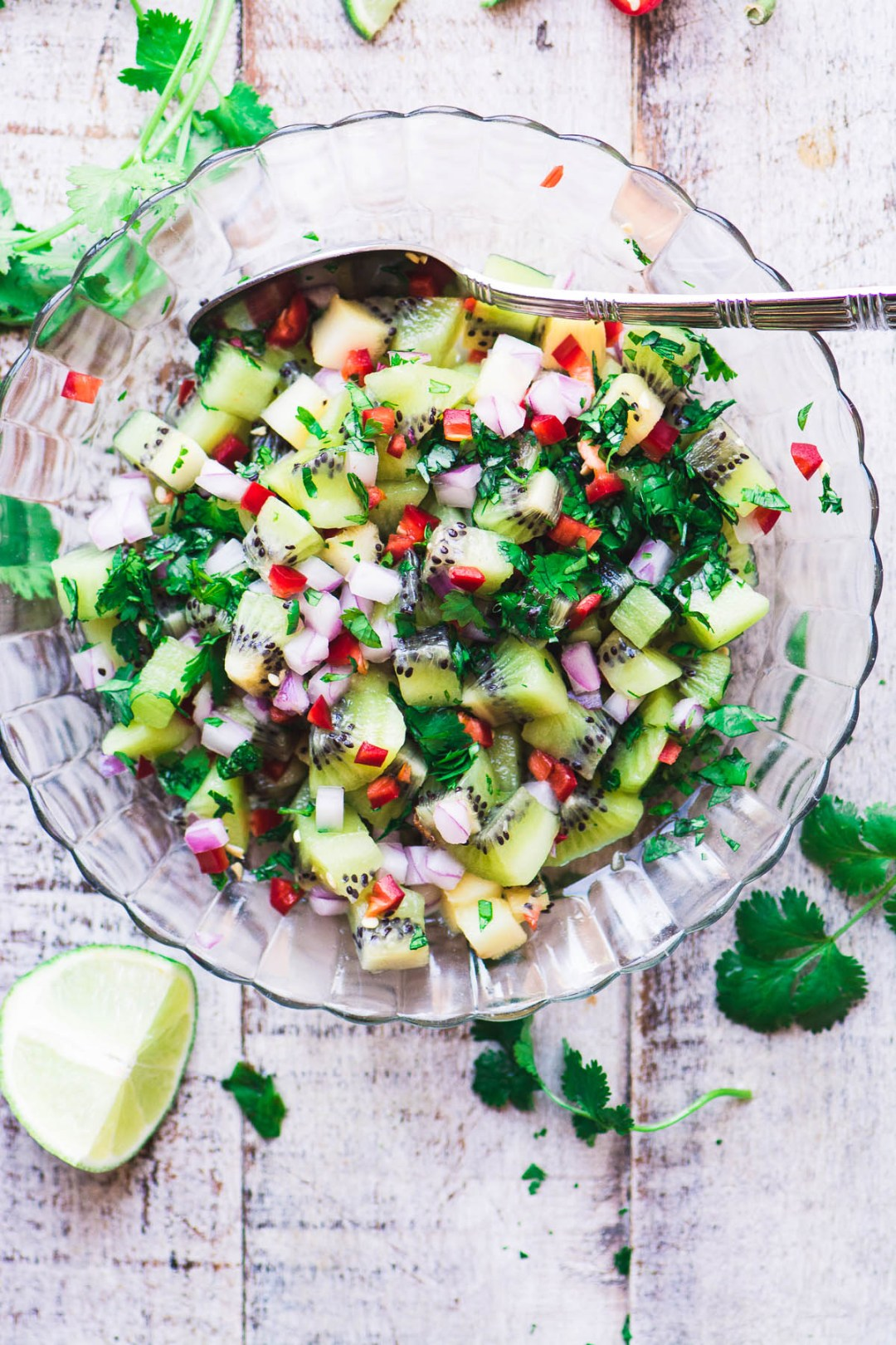 spicy kiwi salsa in a glass bowl on a wooden surface