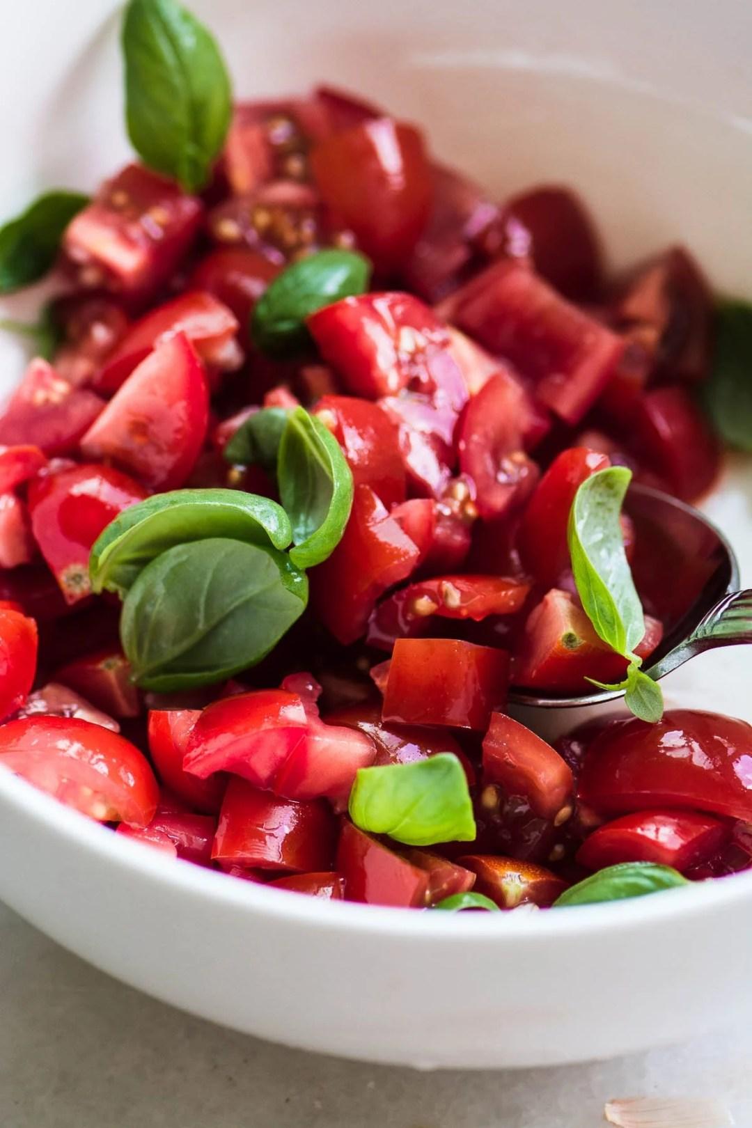 ripe tomatoes in a bowl with basil for pasta alla checca