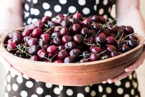 girl holding large wooden bowl of cherries
