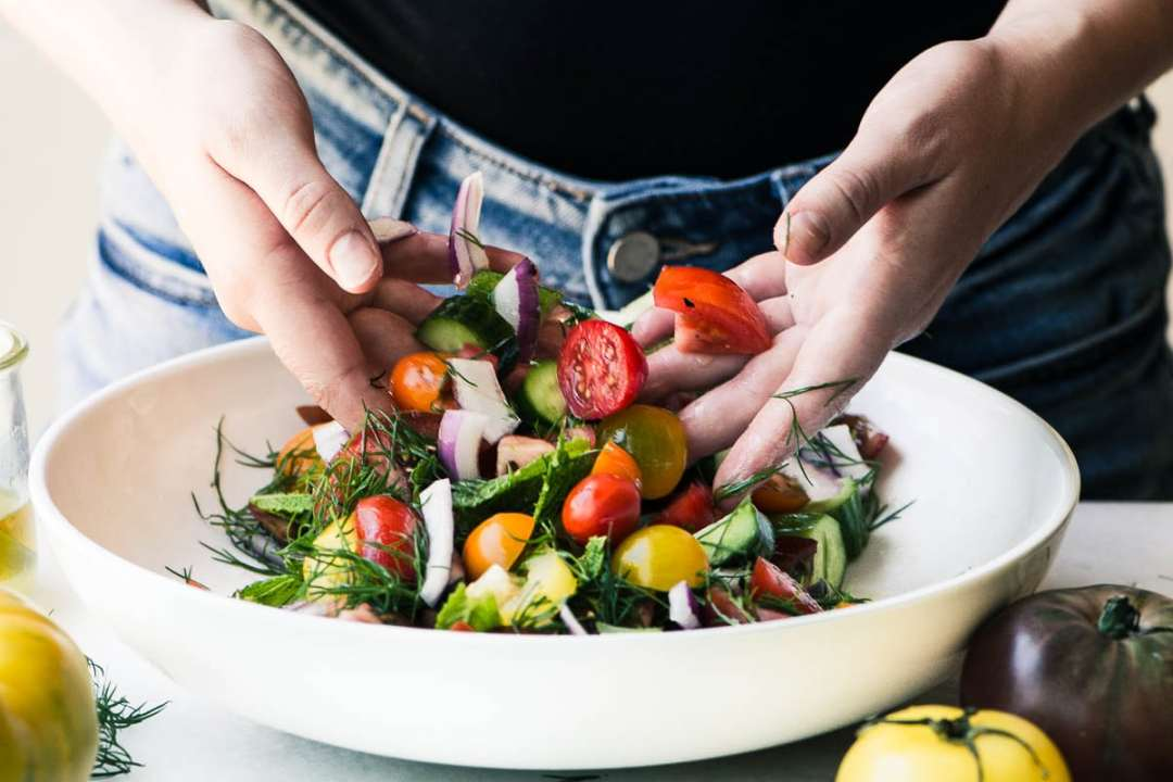 Hands tossing a Shirazi Salad in a white bowl