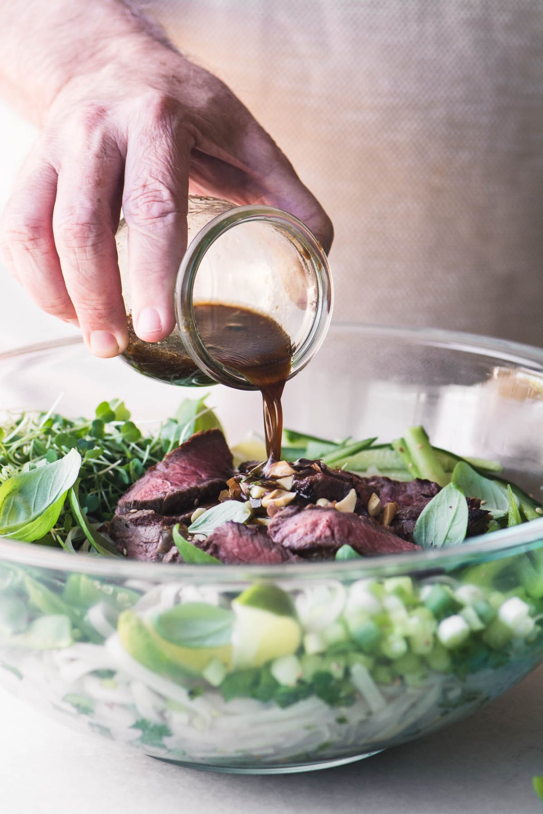Adding dressing to a large glass bowl of Steak Pad Thai Salad