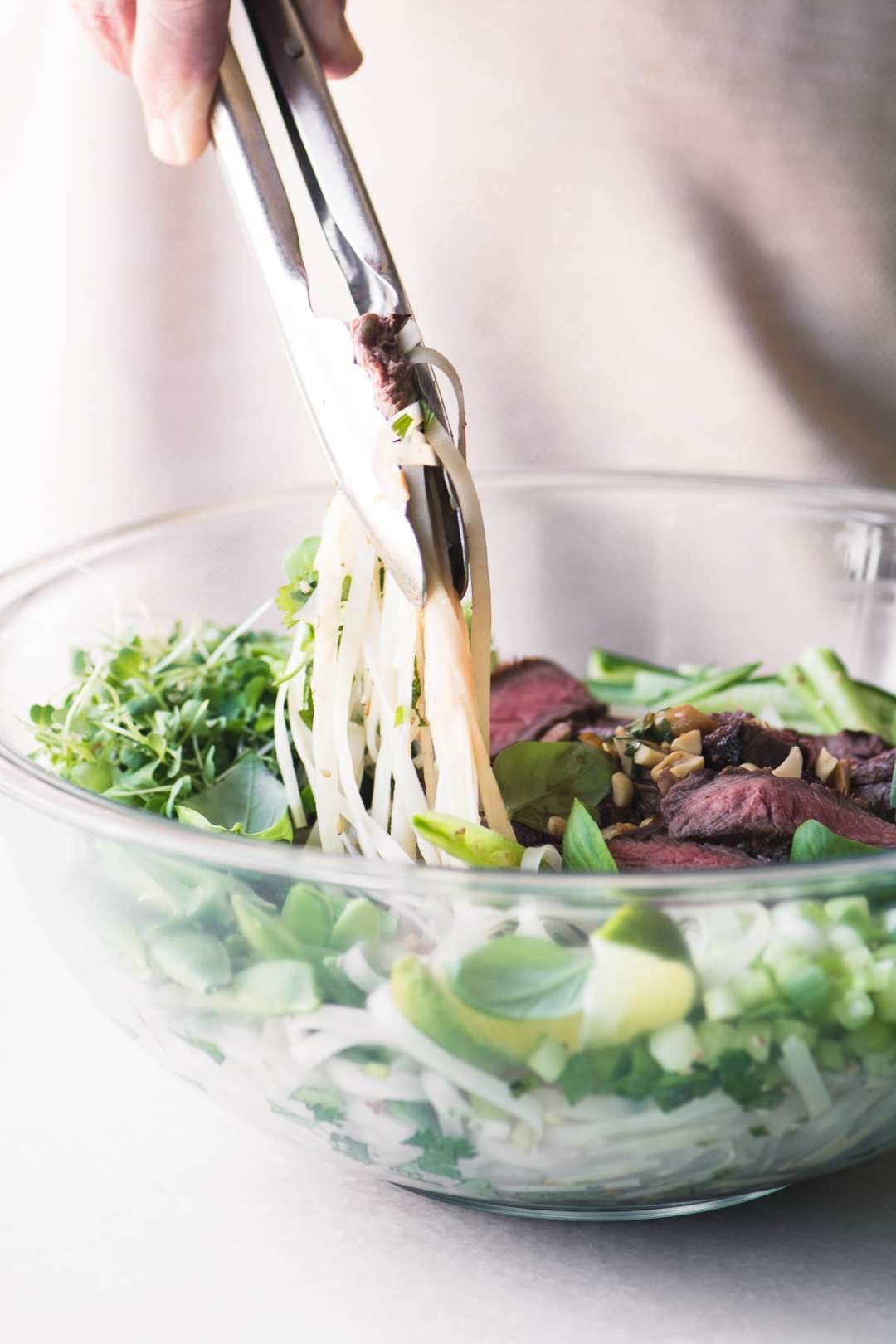 Tossing a big bowl of steak pad Thai salad with tongs