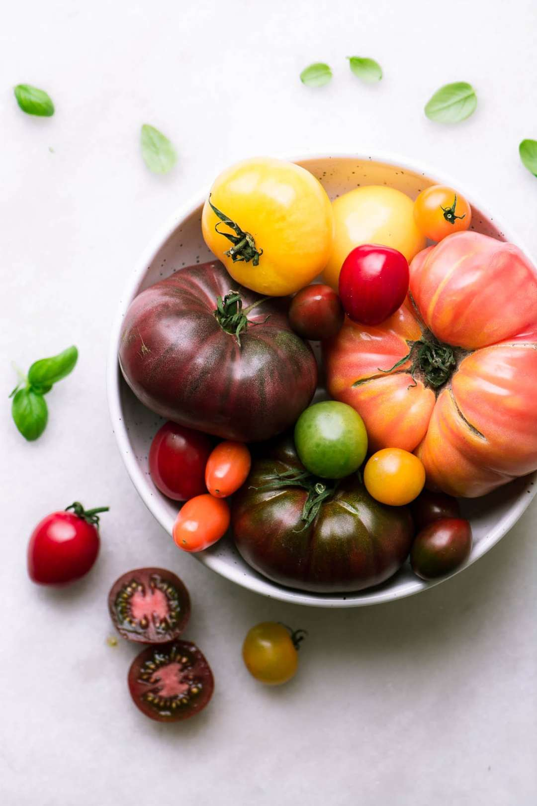 Best Heirloom Tomato Recipes ~ tomatoes in a bowl with basil leaves