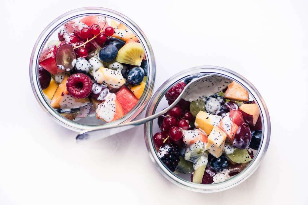 summer fruit salad with kefir poppy seed dressing in two glass bowls