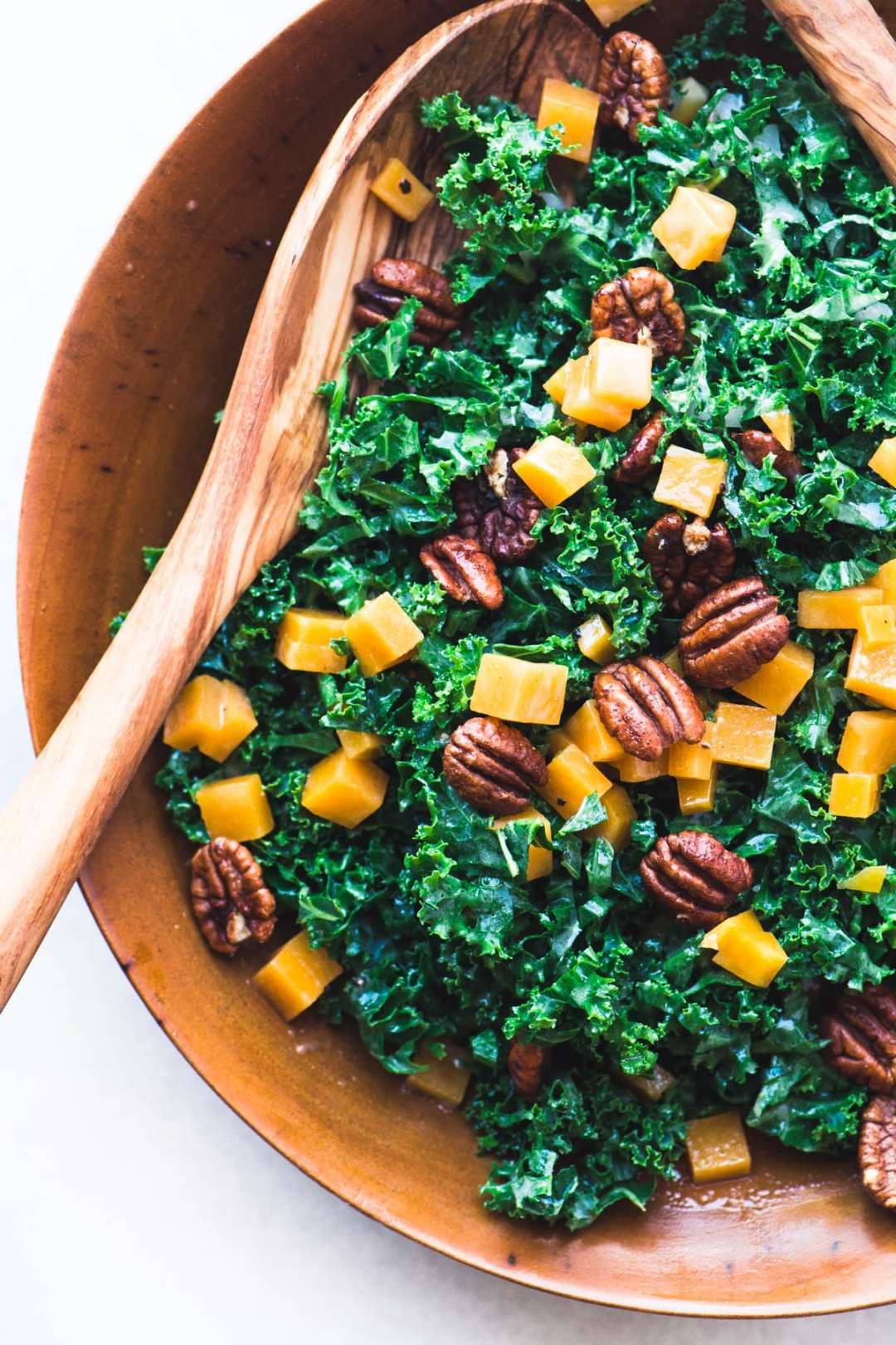 Kale and butternut squash salad in a wooden bowl with wooden salad servers
