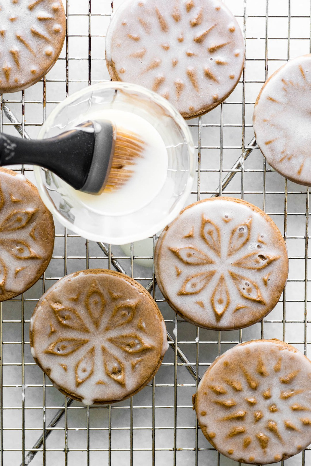Soft Glazed Gingerbread Cookies being brushed with glaze