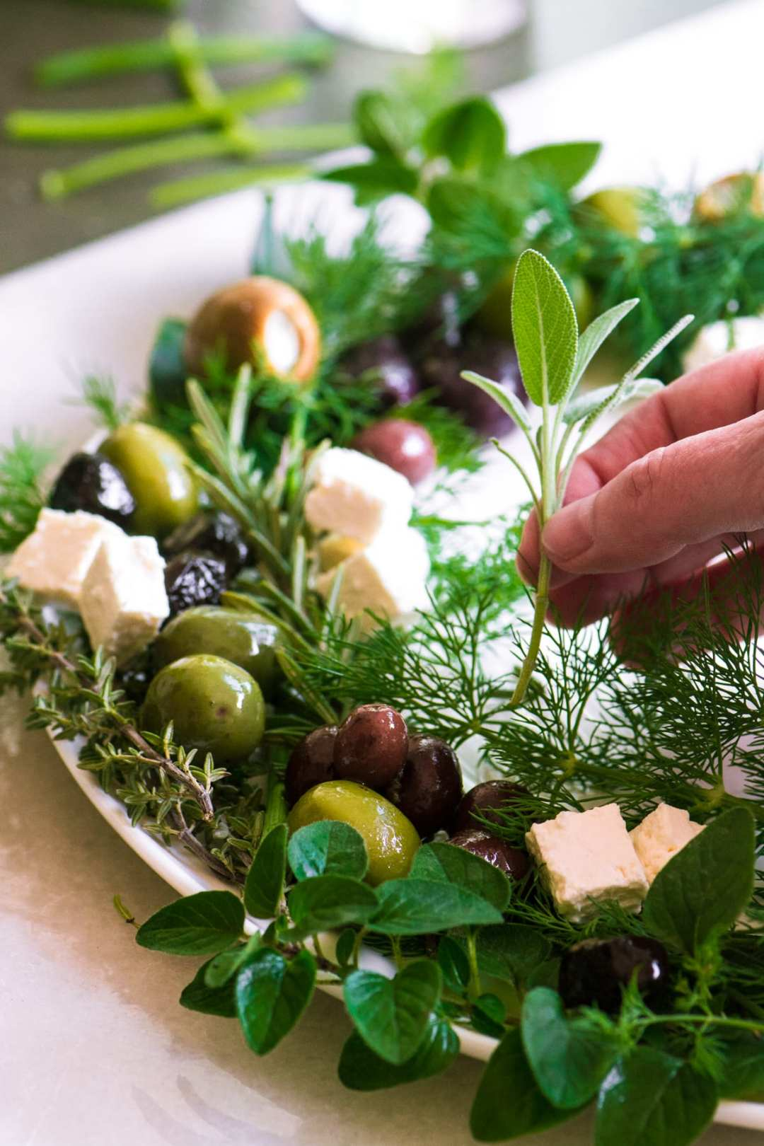 Adding herbs to an Olive and Herb Wreath