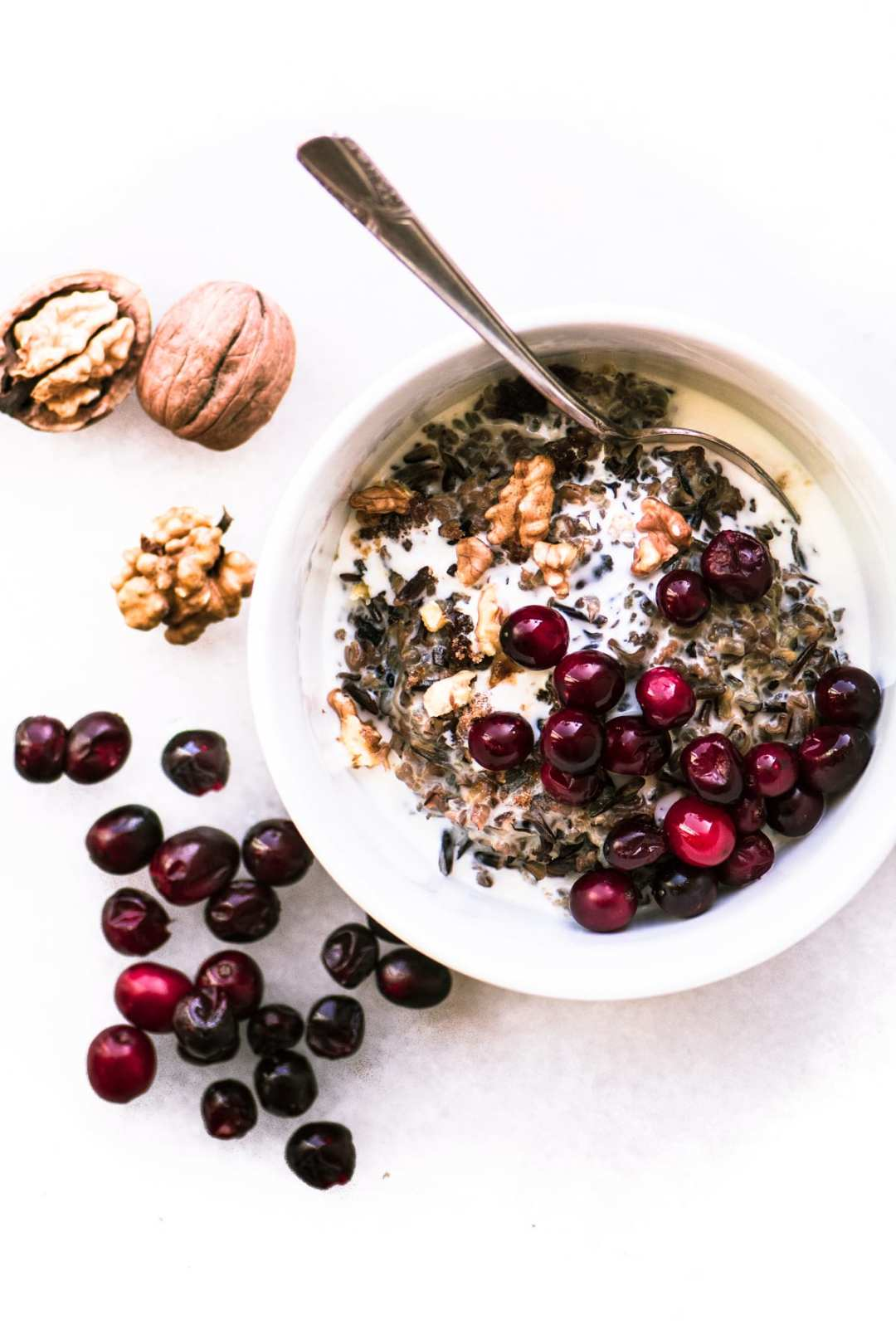 Wild Rice Porridge with cranberries and walnuts in a white bowl with spoon